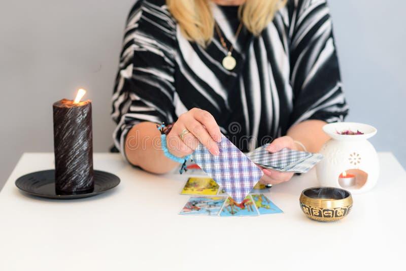 Cierre encima de las manos de la mujer con las cartas de tarot Lectura de la tarjeta Adivinación y clarividencia foto de archivo
