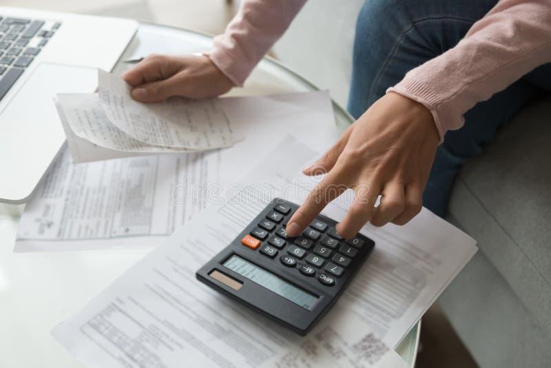 Cierre encima de las manos de la mujer que llevan a cabo el recibo que calcula costos de la compañía fotos de archivo