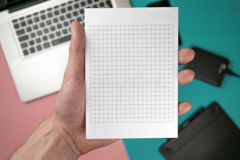 Cierre encima de las manos masculinas que llevan a cabo el espacio en blanco de papel para el papel del dise?o imágenes de archivo libres de regalías