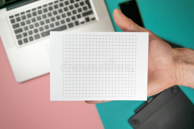 Cierre encima de las manos masculinas que llevan a cabo el espacio en blanco de papel para el papel del dise?o foto de archivo libre de regalías