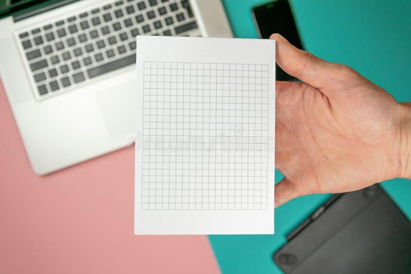 Cierre encima de las manos masculinas que llevan a cabo el espacio en blanco de papel para el papel del dise?o imagen de archivo