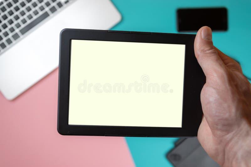 Cierre encima de las manos masculinas que sostienen una tableta en fondo de la tabla de la oficina fotos de archivo libres de regalías