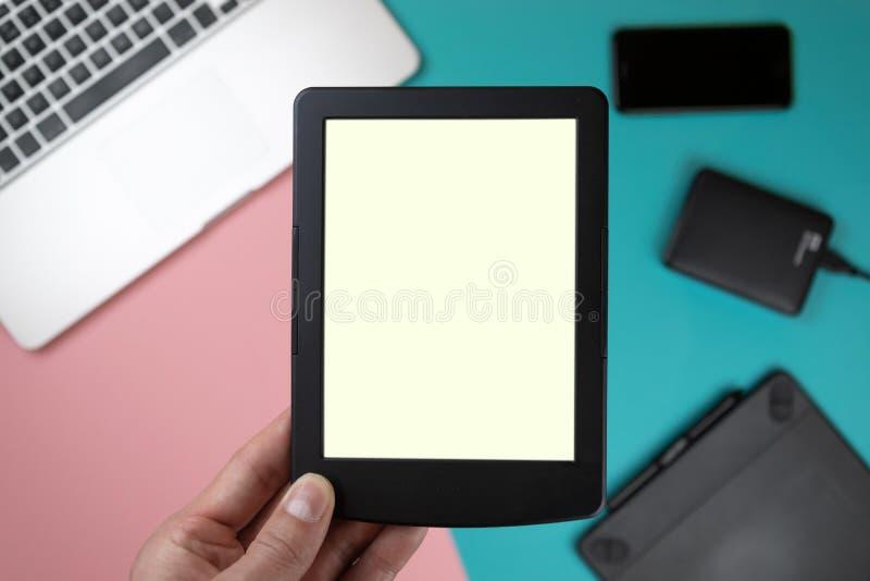 Cierre encima de las manos masculinas que sostienen una tableta en fondo de la tabla de la oficina fotografía de archivo
