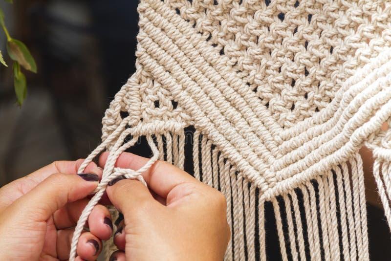 Cierre encima de las manos que tejen la tapicería del agremán con el hilo beige imágenes de archivo libres de regalías