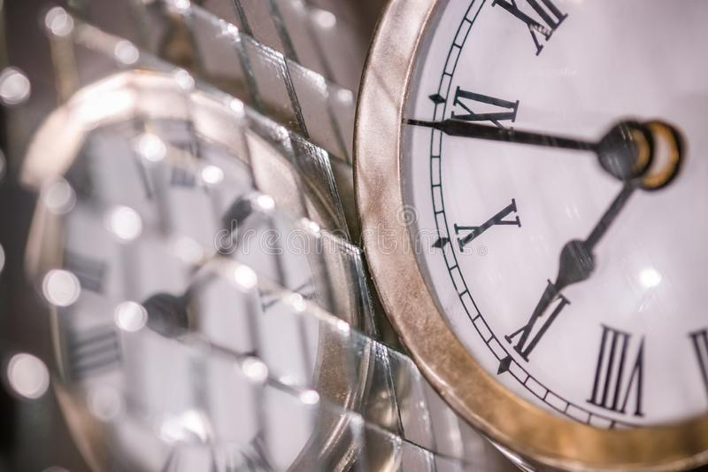 Cierre encima de los arty tirados de un reloj grande del reloj de bolsillo del metal al lado de una bola de discoteca de plata imagen de archivo