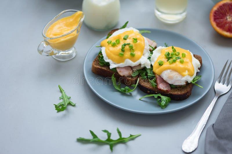 Cierre encima de los huevos Benedicto con arugula, salsa del tocino y del hollandaise en fondo de madera gris Foco suave Concepto fotos de archivo libres de regalías