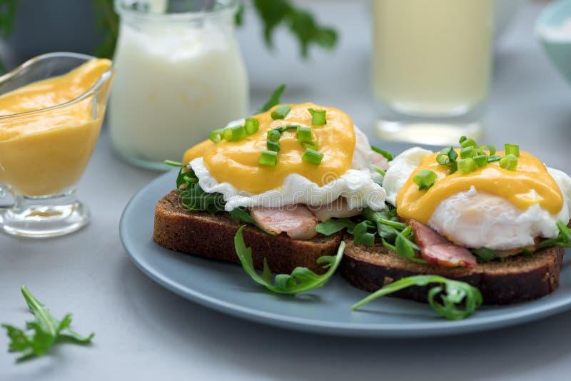 Cierre encima de los huevos Benedicto con arugula, salsa del tocino y del hollandaise en fondo de madera gris Foco suave Concepto imagen de archivo libre de regalías
