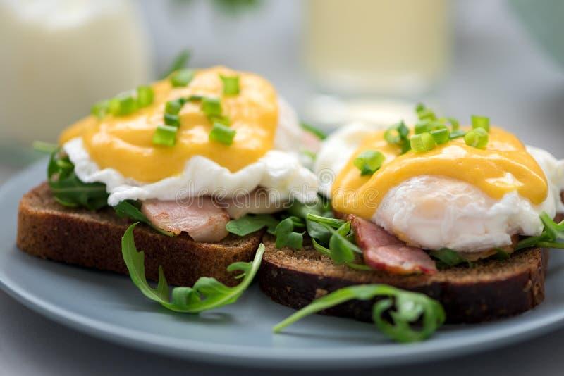 Cierre encima de los huevos Benedicto con arugula, salsa del tocino y del hollandaise en fondo de madera gris Foco suave Concepto imagenes de archivo