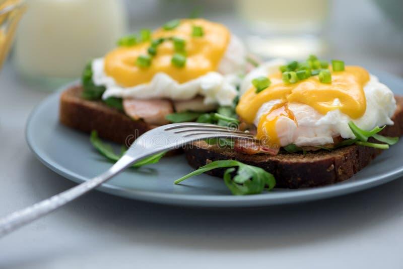 Cierre encima de los huevos Benedicto con arugula, salsa del tocino y del hollandaise en fondo de madera gris Foco suave Concepto fotografía de archivo