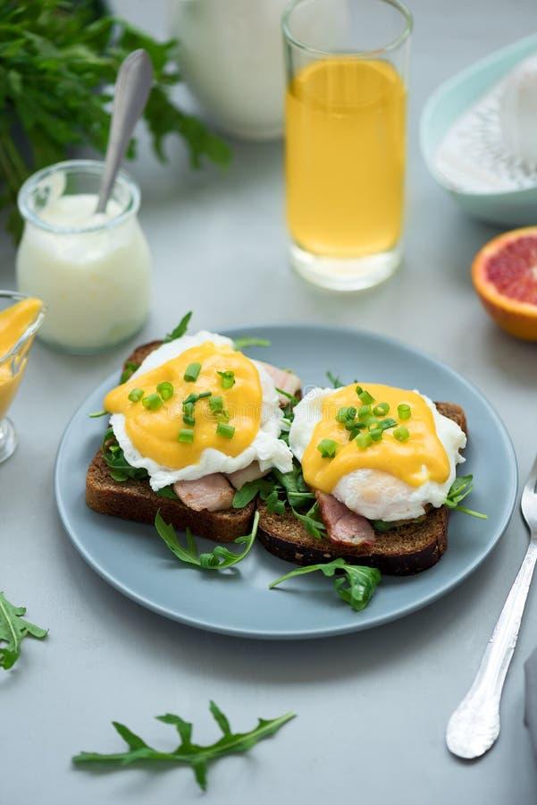 Cierre encima de los huevos Benedicto con arugula, salsa del tocino y del hollandaise en fondo de madera gris Foco suave Concepto foto de archivo libre de regalías