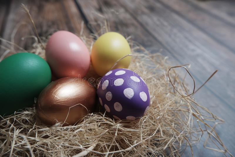 Cierre encima de los huevos de Pascua coloridos en jerarquía en la tabla de madera foto de archivo