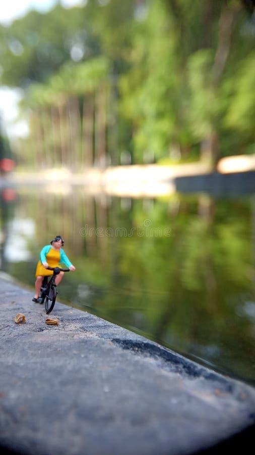 Cierre encima de los juguetes de Mini Figure Woman que montan en bicicleta en la manera de la trayectoria del lado del río con el fotos de archivo