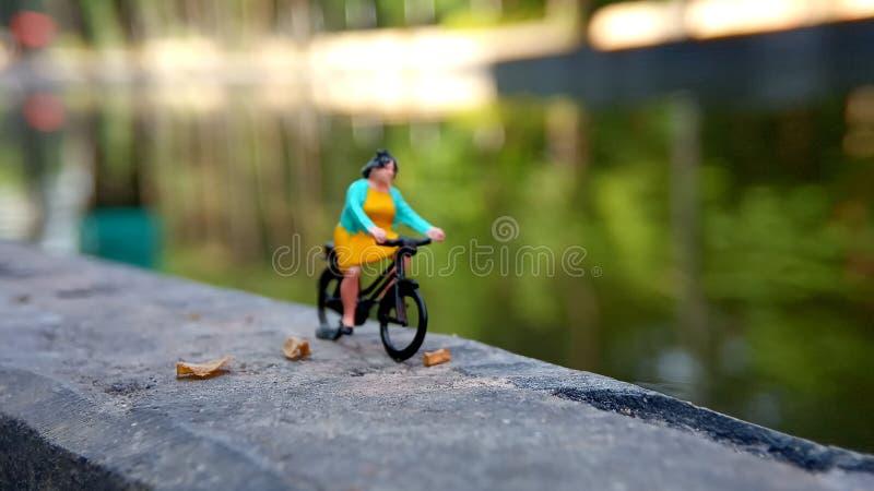 Cierre encima de los juguetes de Mini Figure Woman que montan en bicicleta en la manera de la trayectoria del lado del río con el imagen de archivo libre de regalías