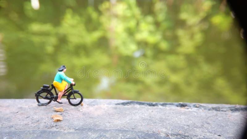 Cierre encima de los juguetes de Mini Figure Woman que montan en bicicleta en la manera de la trayectoria del lado del río con el fotografía de archivo