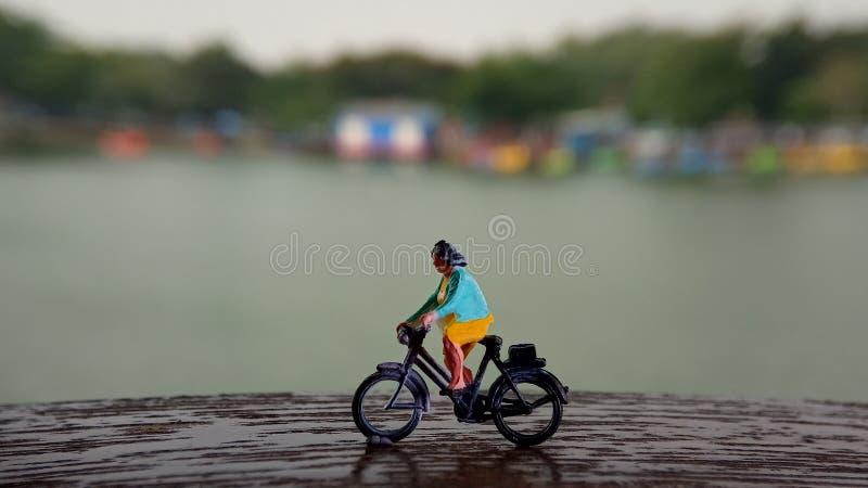 Cierre encima de los juguetes de Mini Figure Woman que montan en bicicleta en la manera de la trayectoria del lado del río con el foto de archivo libre de regalías