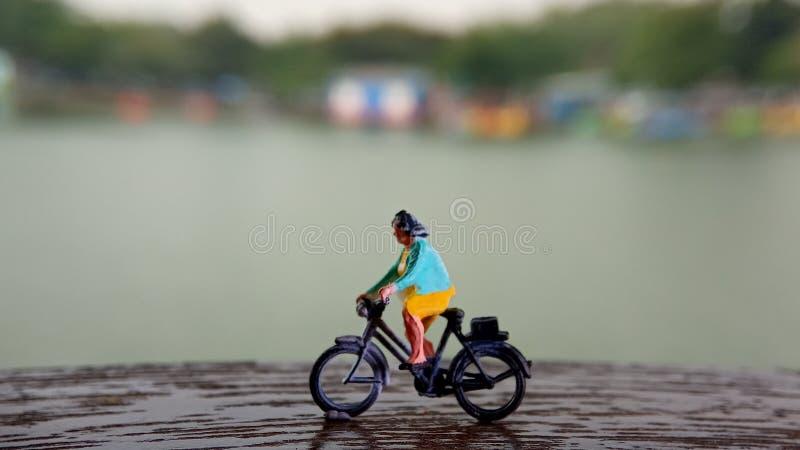 Cierre encima de los juguetes de Mini Figure Woman que montan en bicicleta en la manera de la trayectoria del lado del río con el fotos de archivo libres de regalías