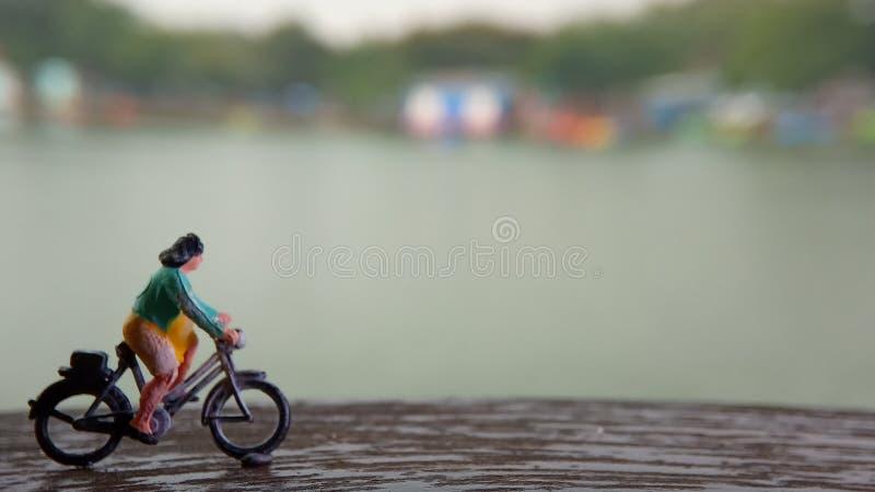 Cierre encima de los juguetes de Mini Figure Woman que montan en bicicleta en la manera de la trayectoria del lado del río con el imagenes de archivo