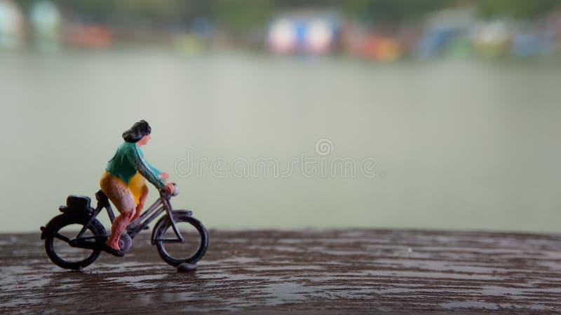 Cierre encima de los juguetes de Mini Figure Woman que montan en bicicleta en la manera de la trayectoria del lado del río con el imagen de archivo
