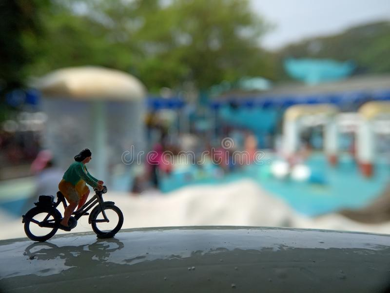 Cierre encima de los juguetes de Mini Figure Woman que montan en bicicleta en la piscina horizontal blanca del parque del agua co fotos de archivo libres de regalías