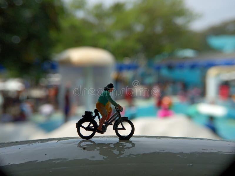 Cierre encima de los juguetes de Mini Figure Woman que montan en bicicleta en la piscina horizontal blanca del parque del agua co imagen de archivo