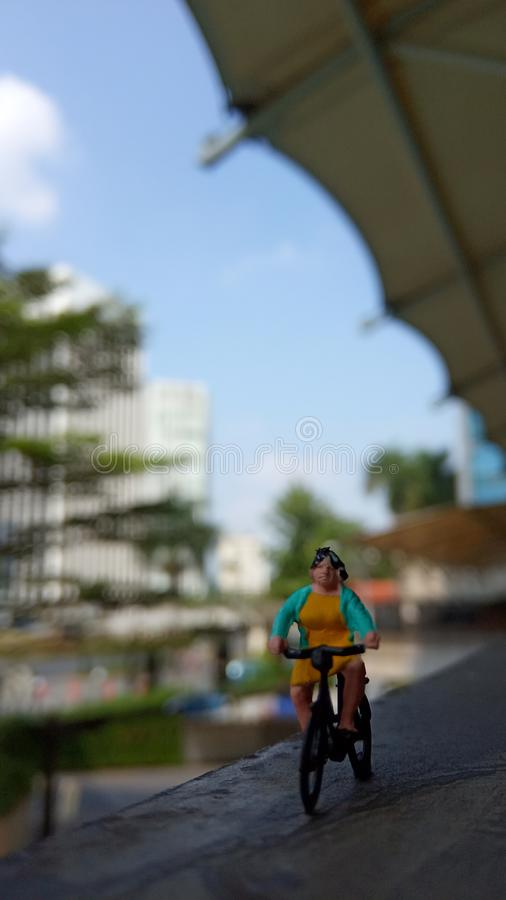 Cierre encima de los juguetes de Mini Figure Woman que montan en bicicleta en la puerta constructiva con el espacio negativo o de imagen de archivo