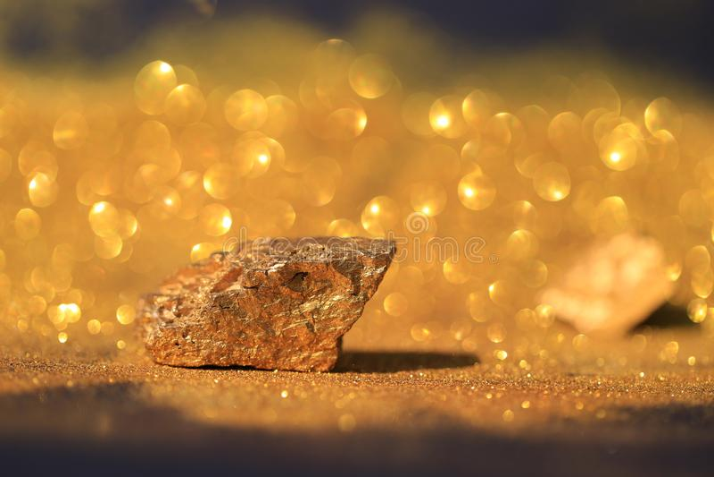 Cierre encima de los minerales puros del oro con la luz de oro en concepto negro del fondo, de la inversión y del negocio imagen de archivo