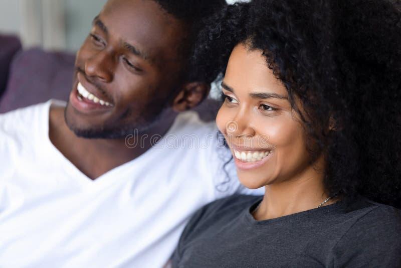 Cierre encima de los pares afroamericanos felices que se sientan junto en el sofá fotografía de archivo libre de regalías