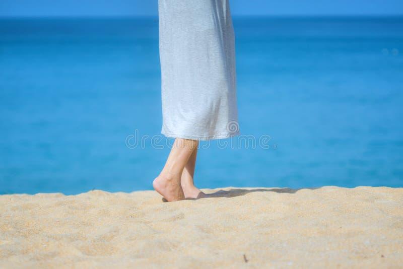 Cierre encima de los pies femeninos jovenes hermosos descalzo que caminan en la playa de la arena con el fondo del mar y del ciel foto de archivo libre de regalías