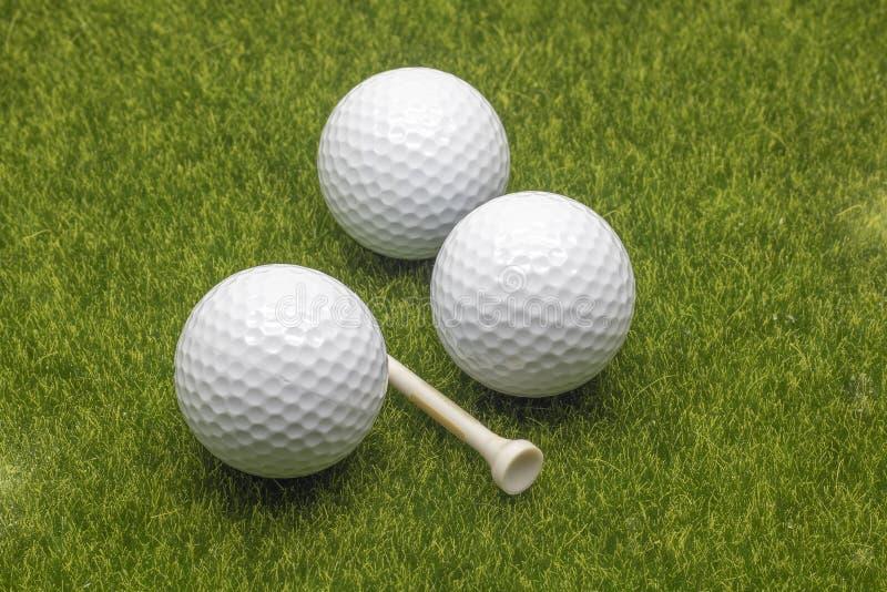 Cierre encima de pelotas de golf y de la camiseta de la visión en fondo de la hierba fotos de archivo libres de regalías