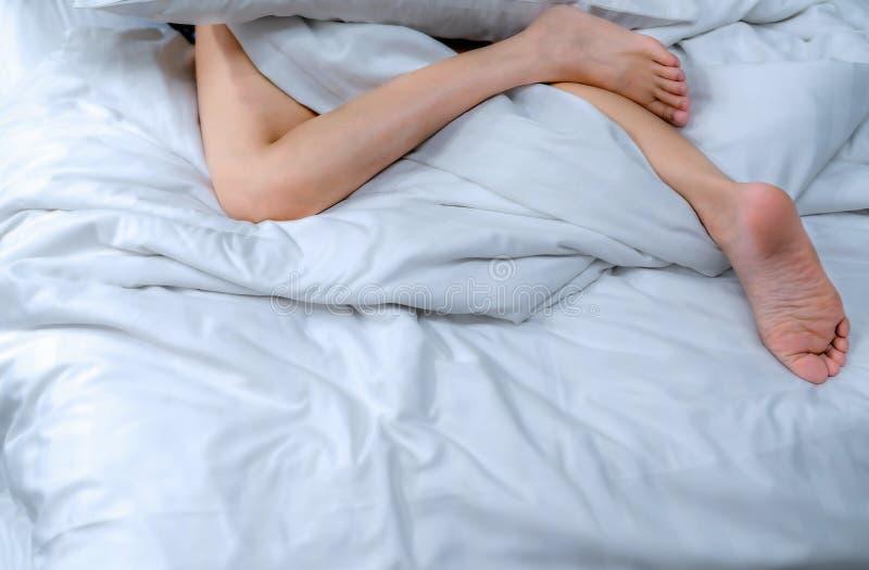 Cierre encima de pies desnudos de la mujer en la cama sobre la manta y la sábana blancas en el dormitorio del hogar o del hotel D fotografía de archivo libre de regalías