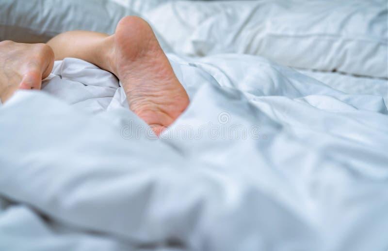 Cierre encima de pies desnudos de la mujer en la cama sobre la manta y la sábana blancas en el dormitorio del hogar o del hotel D foto de archivo libre de regalías