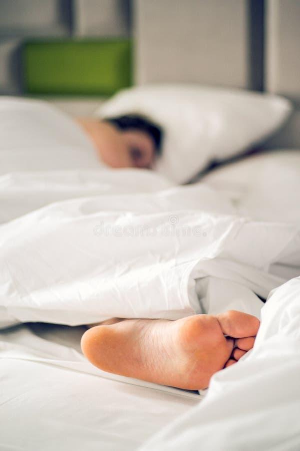 Cierre encima de pies desnudos de la mujer en la cama sobre la manta y la sábana blancas en el dormitorio del hogar o del hotel D imágenes de archivo libres de regalías