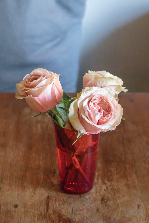 Cierre encima de rosas rosadas hermosas en vidrio rojo en el fondo de madera de la tabla Concepto suave del vintage de la flor imagenes de archivo