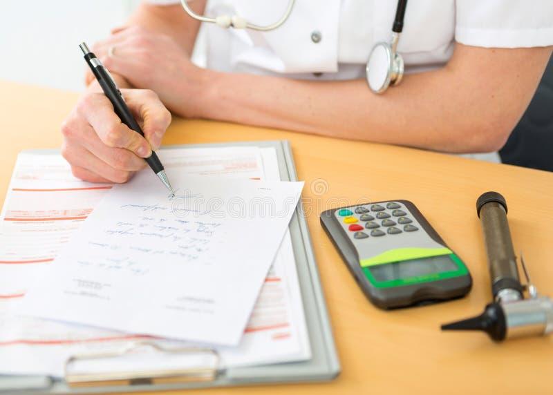 Cierre encima de viewof a un doctor que llena una prescripción a un paciente imágenes de archivo libres de regalías