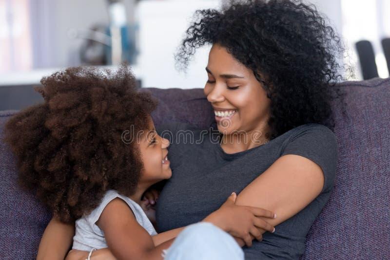 Cierre encima del abarcamiento afroamericano sonriente de la madre y de la hija fotografía de archivo libre de regalías