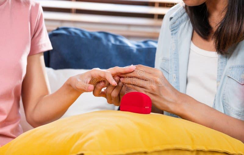 Cierre encima del anillo de la oferta de la lesbiana asiática de los pares que lleva para casarse en la sala de estar en casa Con imagenes de archivo