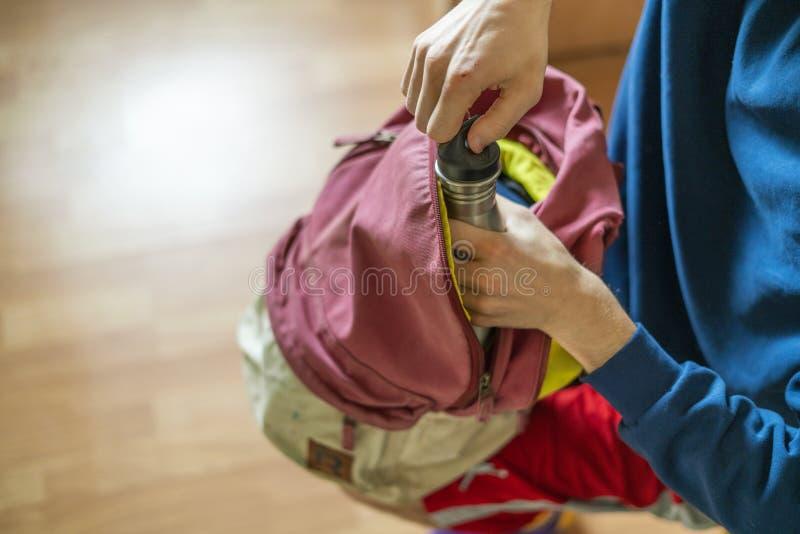 Cierre encima del atleta que toma cosas de las fuentes del deporte de su bolso antes de la práctica f imágenes de archivo libres de regalías