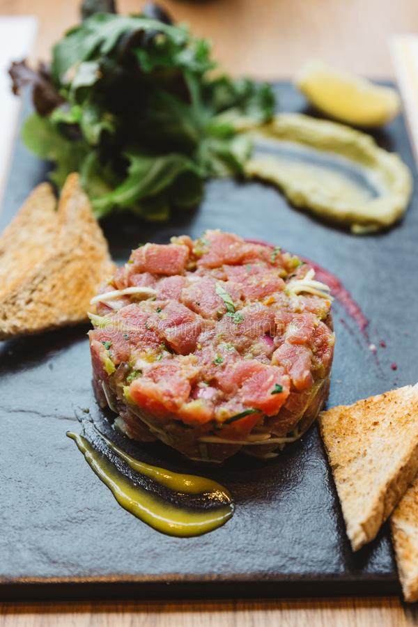 Cierre encima del Bluefin picante Tuna Tartare con la salsa amarga y picante Servido con la tostada y la ensalada en la placa de  imagen de archivo libre de regalías