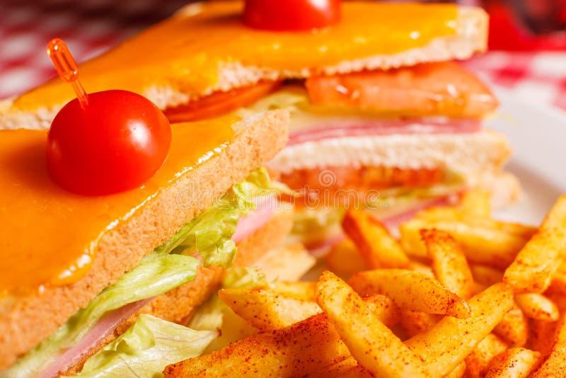 Cierre encima del bocadillo asado a la parrilla sabroso en el restaurante Bocadillo de club con el jamón, el tomate, el queso y l imagen de archivo libre de regalías