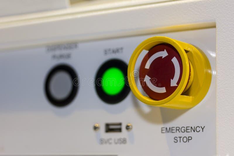 Cierre encima del botón de paro de emergencia en el panel de control de la máquina para la seguridad en la fábrica imagen de archivo
