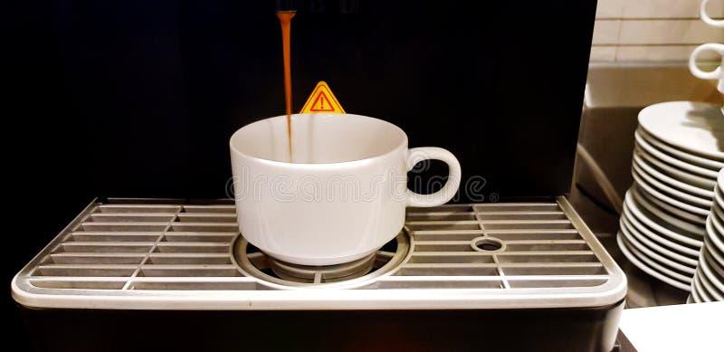 Cierre encima del café caliente que vierte de la máquina fresca del fabricante de café en la taza blanca fotos de archivo libres de regalías