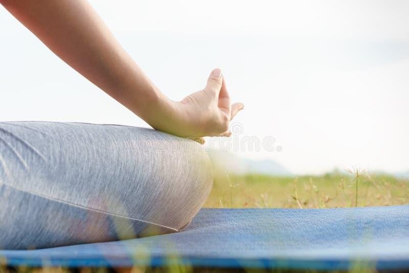 Cierre encima del cuerpo de la mano y de la mitad de la mujer de la salud sentarse en la posici?n de la yoga del loto en la ma?an fotografía de archivo libre de regalías