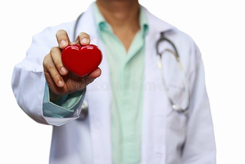 Cierre encima del doctor de sexo masculino con el corazón rojo aislado en el fondo blanco imagen de archivo