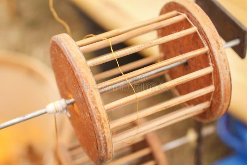 Cierre encima del equipo de madera que aspa el hilo de los capullos del gusano de seda del oro en pote en la estufa del carbón de imagen de archivo libre de regalías
