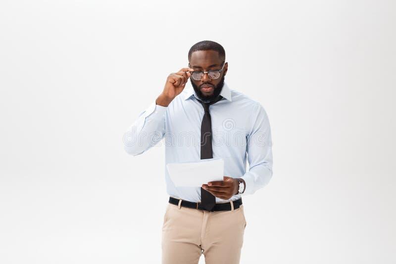 Cierre encima del hombre de negocios afroamericano joven con la mirada de la cámara mientras que sostiene el papel del documento imagenes de archivo