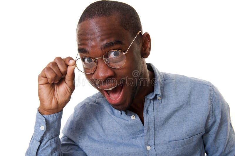 Cierre encima del hombre de negocios joven con los vidrios y la expresión sorprendida imagenes de archivo