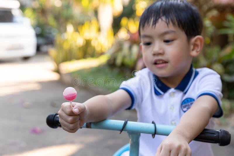 Cierre encima del muchacho asiático joven que sostiene una piruleta foto de archivo libre de regalías