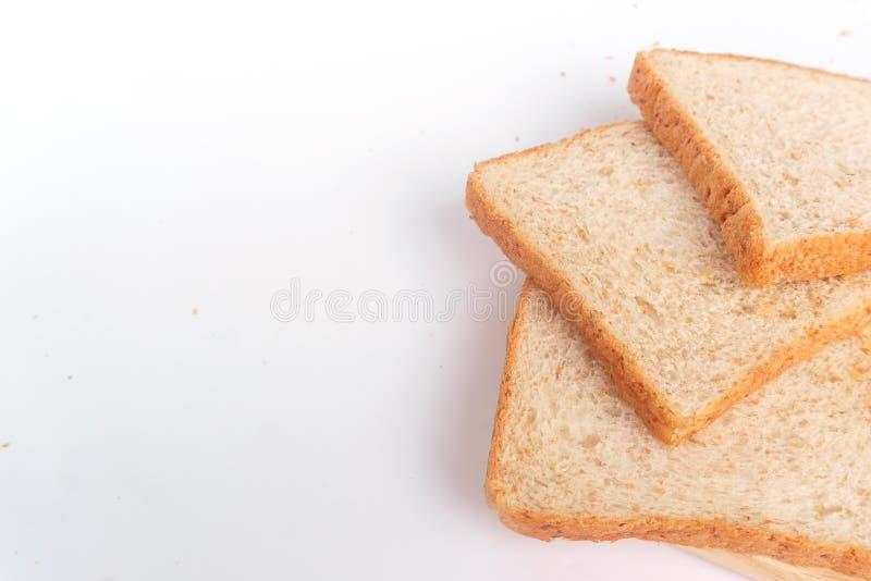 Cierre encima del pan cortado marrón del trigo integral aislado en el fondo blanco Preparación hecha en casa sana del desayuno de imagen de archivo