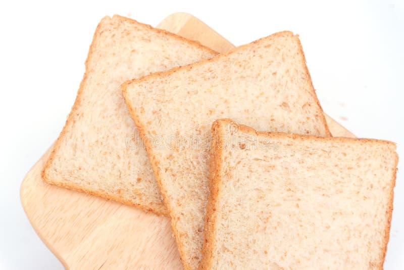 Cierre encima del pan cortado marrón del trigo integral aislado en el fondo blanco Preparación hecha en casa sana del desayuno de fotografía de archivo