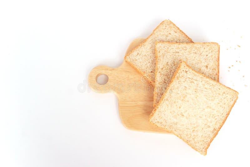 Cierre encima del pan cortado marrón del trigo integral aislado en el fondo blanco Preparación hecha en casa sana del desayuno de imagenes de archivo
